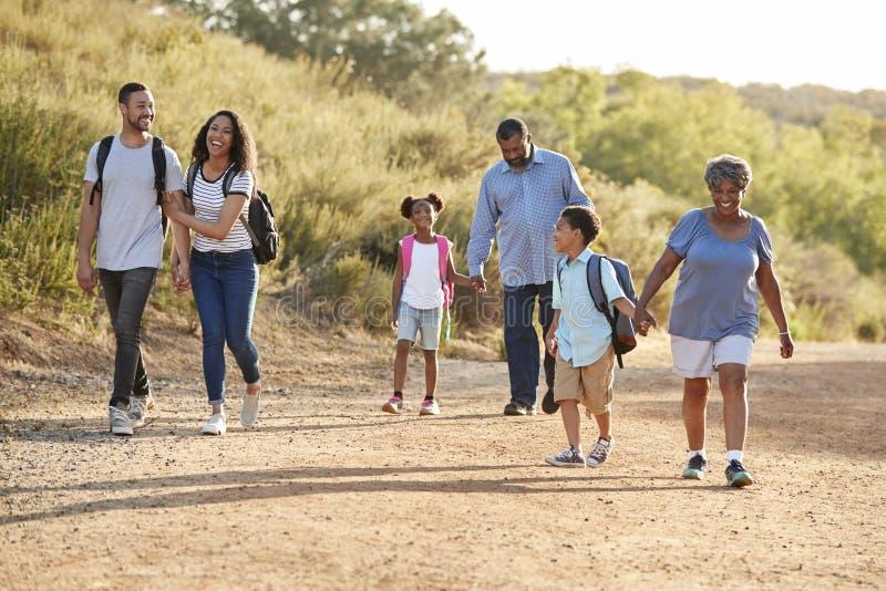 Multi Generations-Familien-tragende Rucksäcke, die zusammen in der Landschaft wandern lizenzfreie stockfotografie