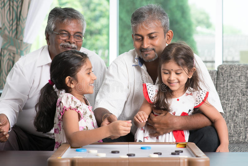 Multi generations family playing games together. Happy multi generations Asian Indian family playing carom game at home. Grandparent, parent and children indoor stock images