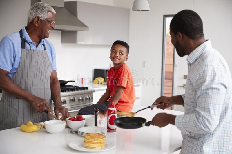 Multi Generations-männliche Familie in der Küche zu Hause, die zusammen Pfannkuchen macht stockfotos