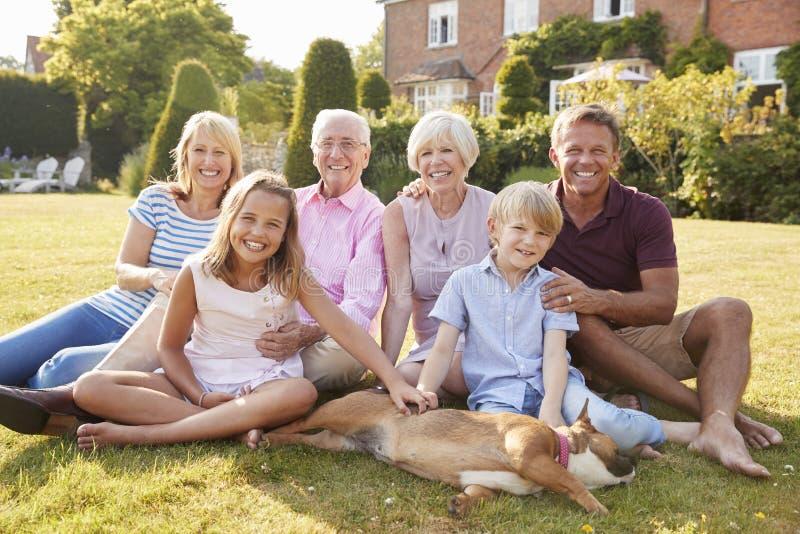 Multi Generationsfamilie, die auf Gras im Garten sitzt stockbilder