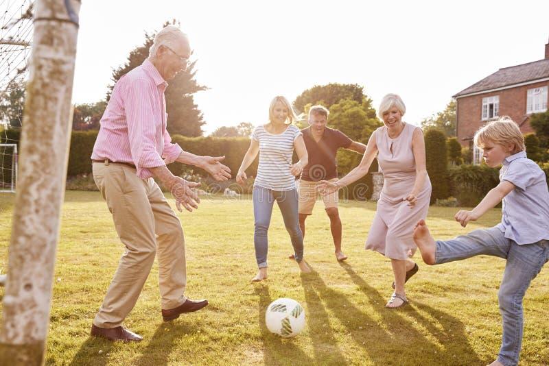 Multi Generationsfamilie, die Fußball im Garten spielt stockfotografie