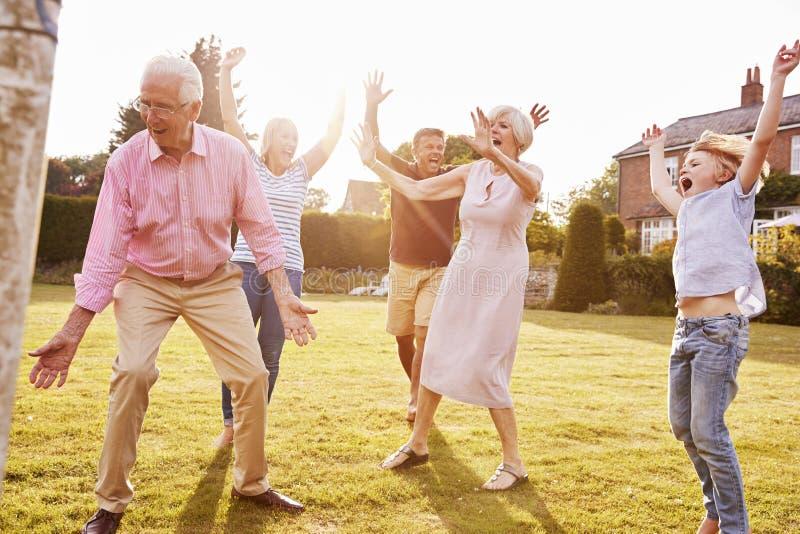 Multi Generationsfamilie, die Fußball im Garten spielt lizenzfreies stockbild