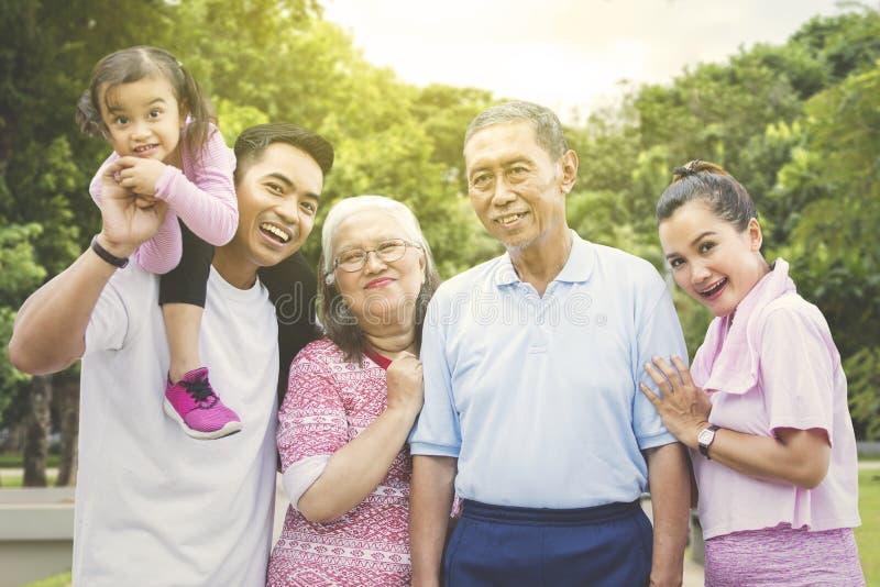 Multi Generationsfamilie, die im Park lächelt lizenzfreie stockfotografie