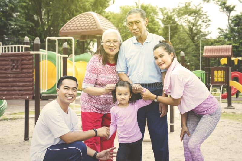Multi Generationsfamilie, die im Spielplatz lächelt lizenzfreie stockbilder