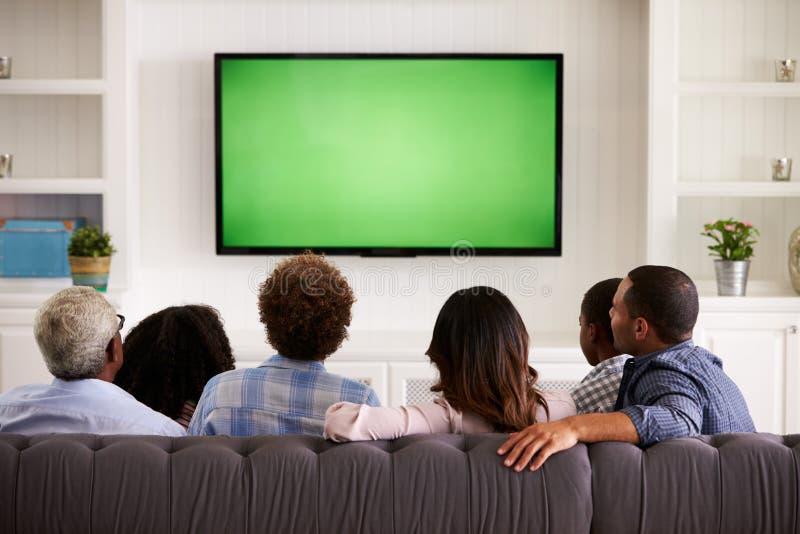Multi Generationsfamilie, die zu Hause, hintere Ansicht fernsieht lizenzfreie stockbilder