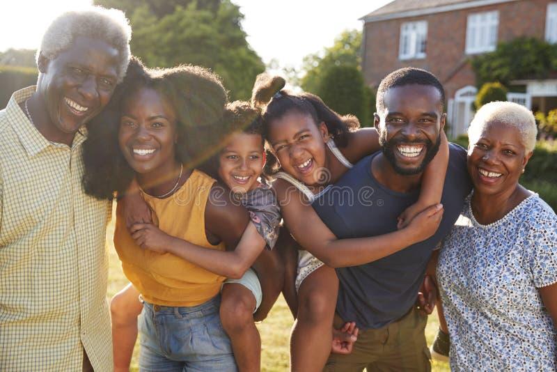 Multi Generationsschwarzfamilie, Eltern, die Kinder huckepack tragen lizenzfreies stockfoto