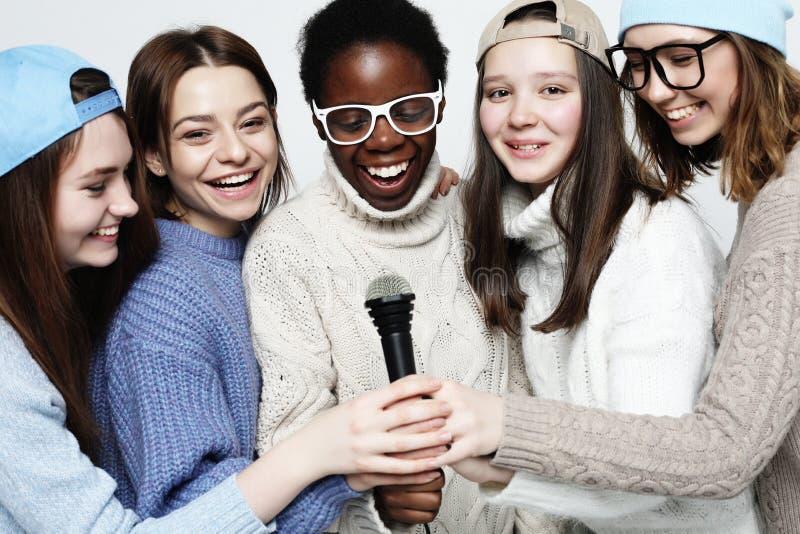 Multi grupo diverso das meninas da nação, empresa adolescente dos amigos alegre tendo o divertimento com microfone fotografia de stock