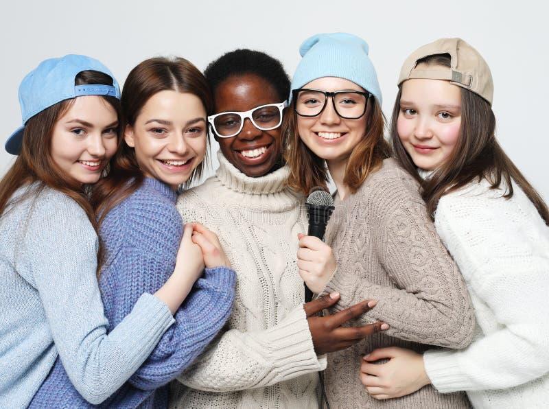 Multi grupo diverso das meninas da nação, empresa adolescente dos amigos alegre tendo o divertimento com microfone fotografia de stock royalty free