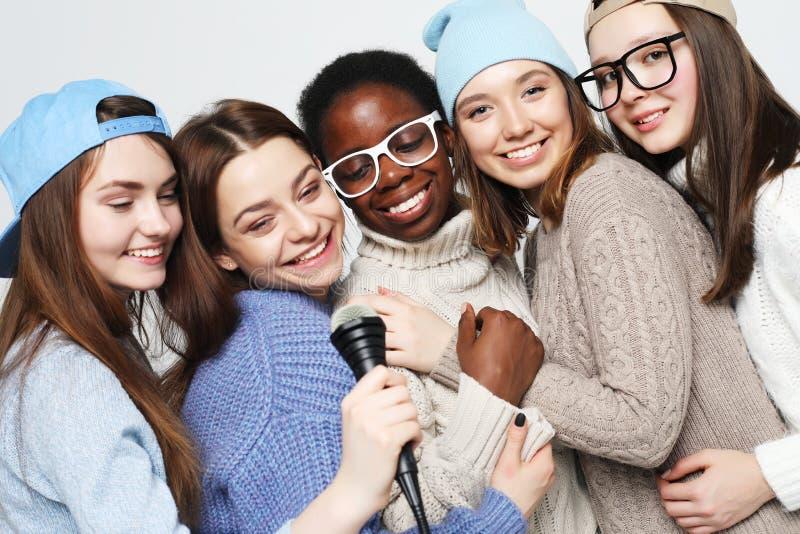 Multi grupo diverso das meninas da na??o, empresa adolescente dos amigos alegre tendo o divertimento com microfone imagens de stock