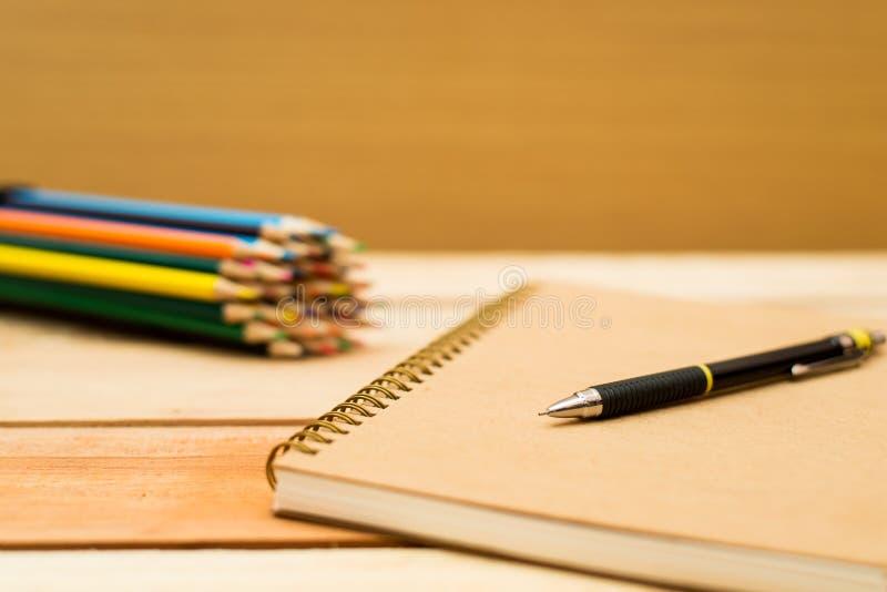 Multi lápis e caderno coloridos com espaço do texto fotografia de stock