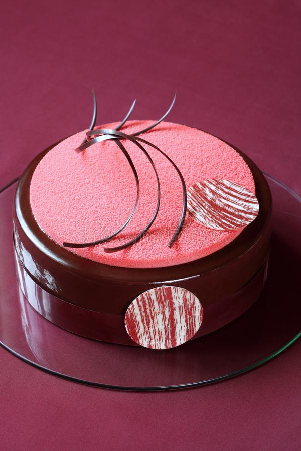 Multi Layered Chocolate Raspberry Mousse Cake. Contemporary Multi Layered Chocolate Raspberry Mousse Cake decorated with chocolate elements, on burgundy stock image