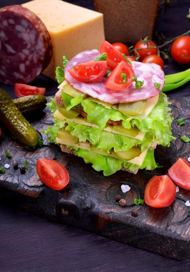 Multi layered club sandwich with rye bread, lettuce salad, sausage, cheese, salted cucumbers and tomatoes. On a dark board royalty free stock photo