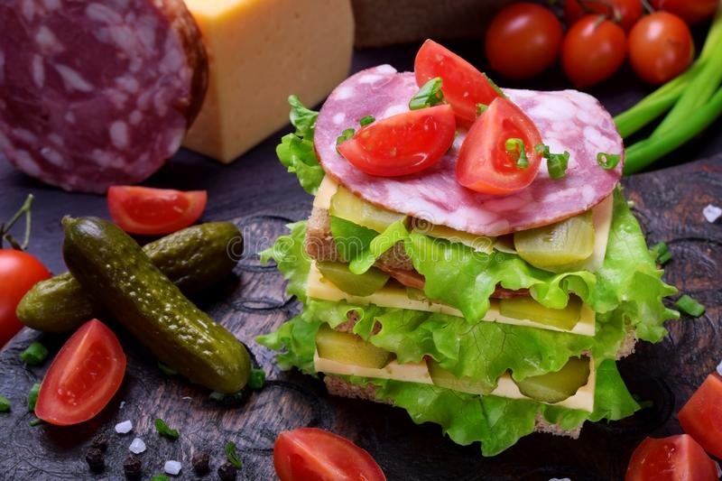 Multi layered club sandwich with rye bread, lettuce salad, sausage, cheese, salted cucumbers and tomatoes. On a dark board stock photos