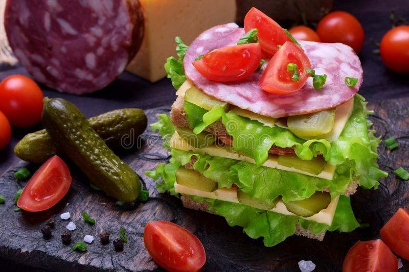Multi layered club sandwich with rye bread, lettuce salad, sausage, cheese, salted cucumbers and tomatoes. On a dark board stock photo