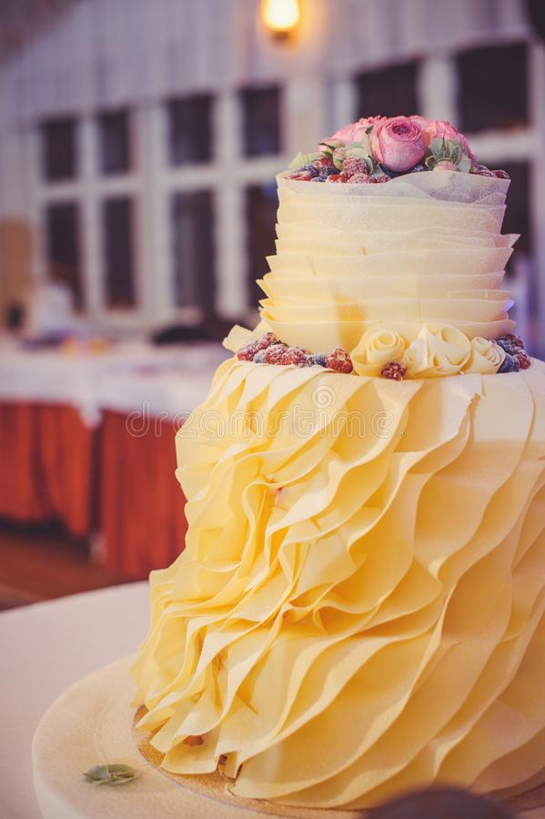 A multi-level beige wedding cake at a celebration in a cozy interior royalty free stock photo