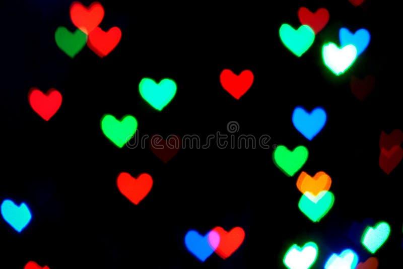 Multi luzes borradas coloridas na forma dos corações na obscuridade ilustração royalty free