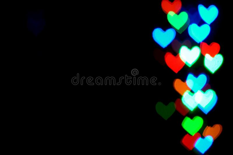 Multi luzes borradas coloridas na forma dos corações na obscuridade ilustração stock