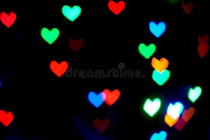 Multi luzes borradas coloridas na forma dos corações na obscuridade ilustração do vetor