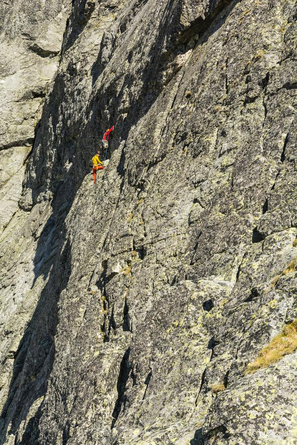Multi-pitch climb - a party of two climbers on the pitch in the wall of the mountain massif. stock photography