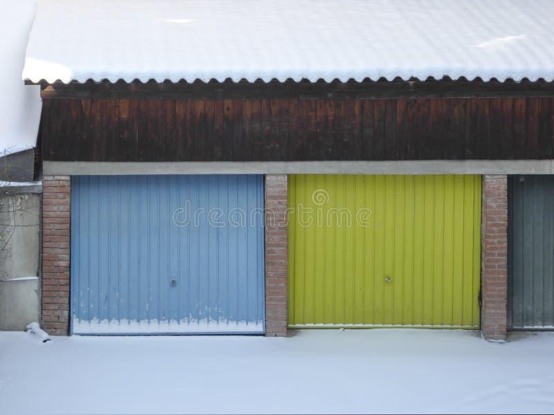 Multi porta da garagem e neve coloridas na frente do garagens imagem de stock