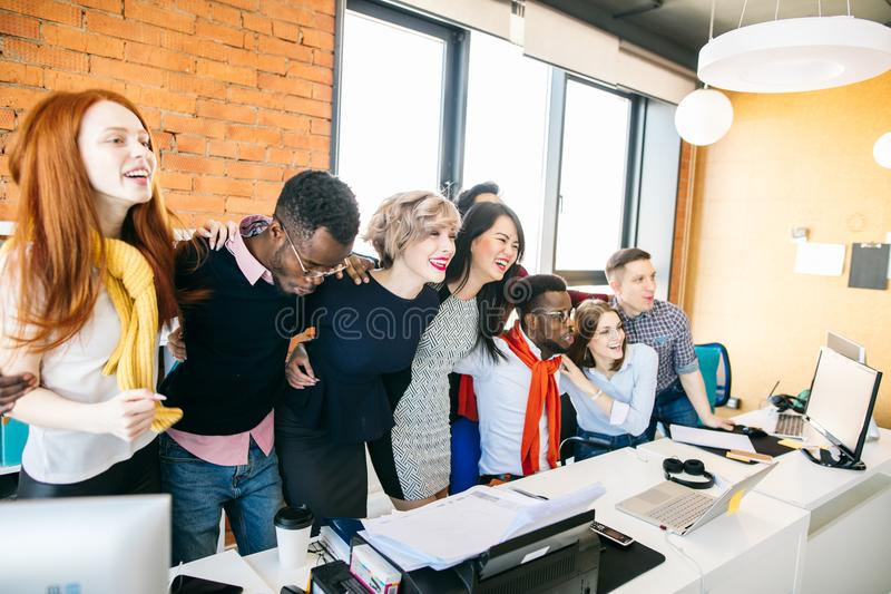 Multi racial co-workers are embracing to show their common intent. Identity of views concept royalty free stock images