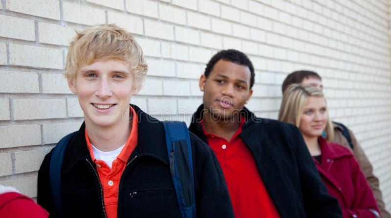 Multi-racial studenten tegen een bakstenen muur stock afbeeldingen