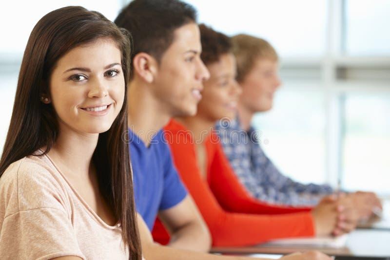 Multi rassen tienerleerlingen die in klasse, één aan camera glimlachen stock afbeelding