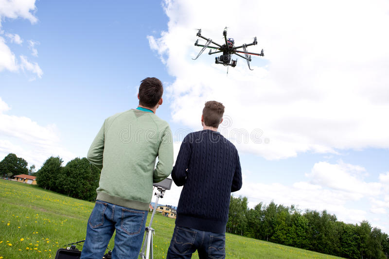 Multi rotor photography UAV. Photography multirotor helicopter being flown by a pilot and photographer stock image