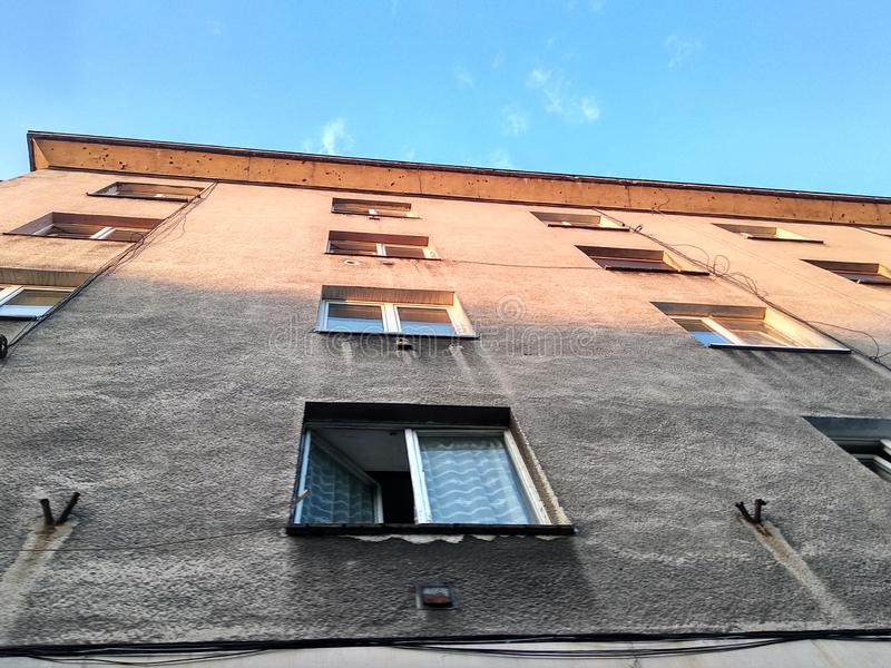 Multi-storey building of the 60s. gray dirty facade of an old house, open window in the apartment, the house against the sky, royalty free stock photos