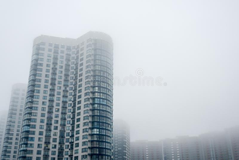 Multi-storey house in the fog. Horizontal frame royalty free stock photo