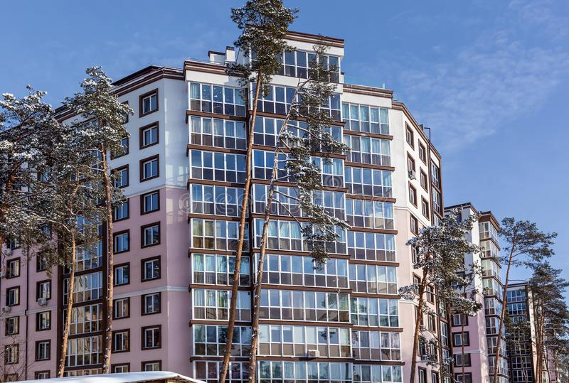 Multi-storey house among the trees. Multi-storey residential building among the snow-covered tops of pines. The facade of the house is visible through tall trees royalty free stock image