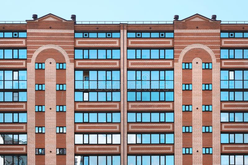 Multi-storey modern house close-up. Brickwork, windows, reflections of sky in glass. Daytime, sun. royalty free stock images