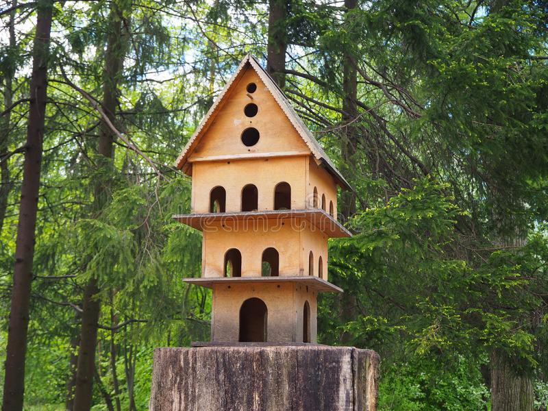 Multi-storey wooden carved birdhouse on a tree stump, a feeder for birds in the park. Multi storey wooden carved birdhouse on a tree stump, a feeder for birds in royalty free stock photo