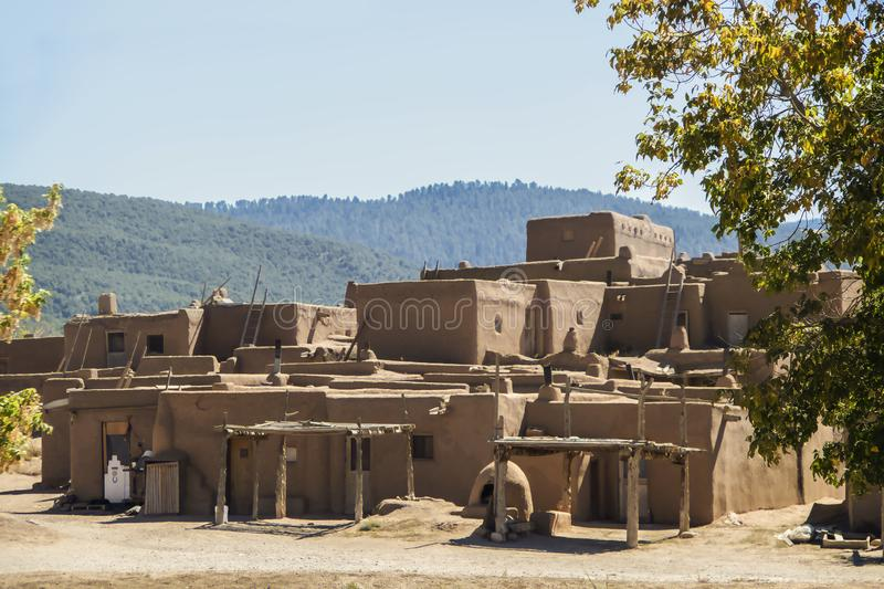 Multi-storied adobe mud Native American pueblo dwelling in the Southwestern United states with drying racks and outside ovens with stock photography