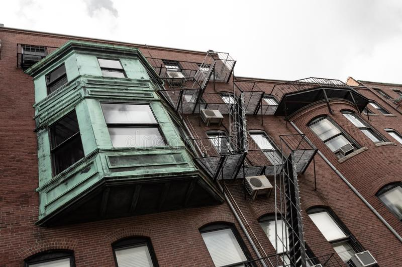 Multi story bumped out bay window with verdigris metal patina on old apartment building stock image