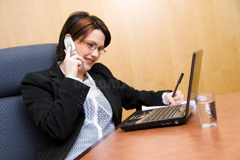 Multi-tasking. Busy woman on the phone and on her laptop royalty free stock photos