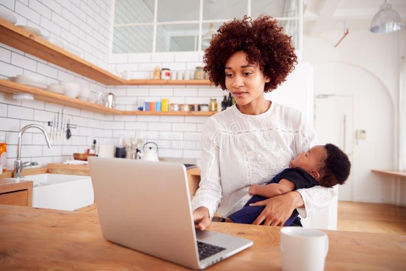 Multi-Tasking Moeder houdt de Zoon van de Slaapbaby en werkt aan Laptop Computer in Keuken royalty-vrije stock fotografie