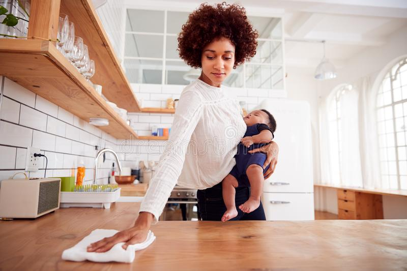 Multi-Tasking Mother Holds Sleeping Baby Son And Cleans In Kitchen stock photography