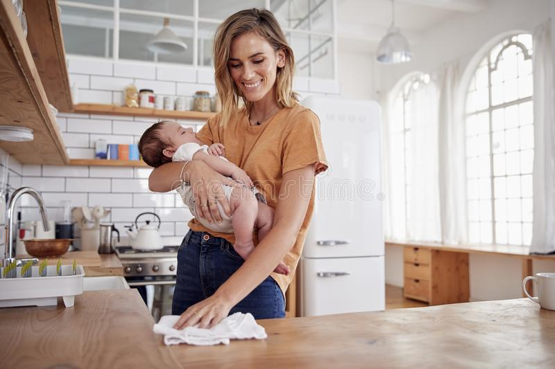 Multi-Tasking Mother Holds Sleeping Baby Son And Cleans In Kitchen stock photo