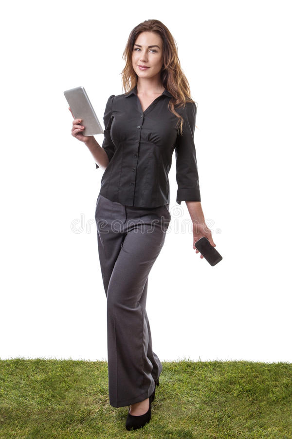 Multi-tasking woman. Pretty young model sanding on grass, holding her tablet computer in one hand and her mobile phone in the other royalty free stock photos