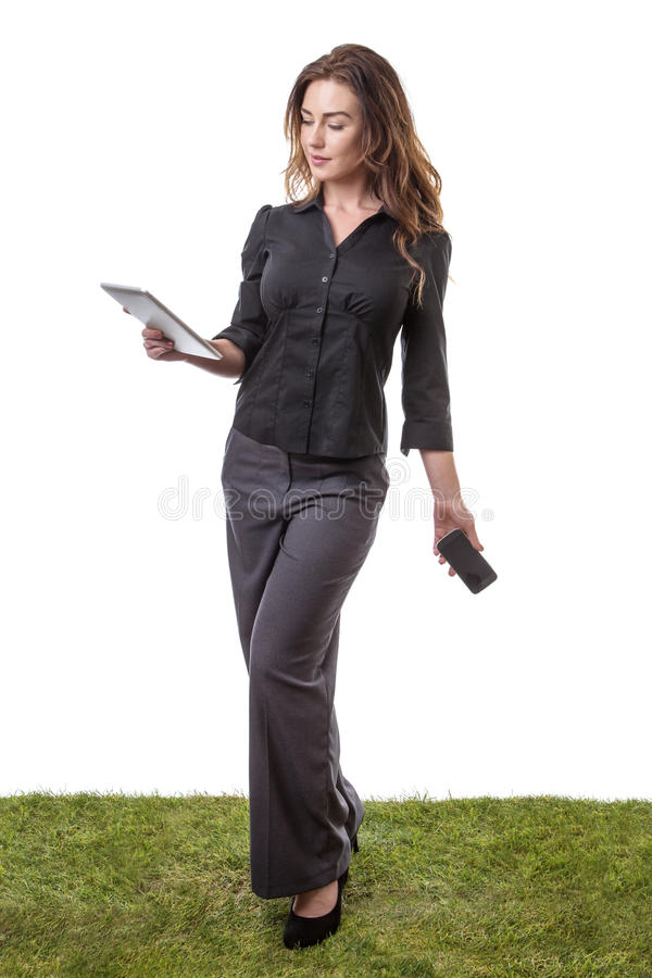 Multi-tasking woman. Pretty young model sanding on grass, holding her tablet computer in one hand and her mobile phone in the other royalty free stock images