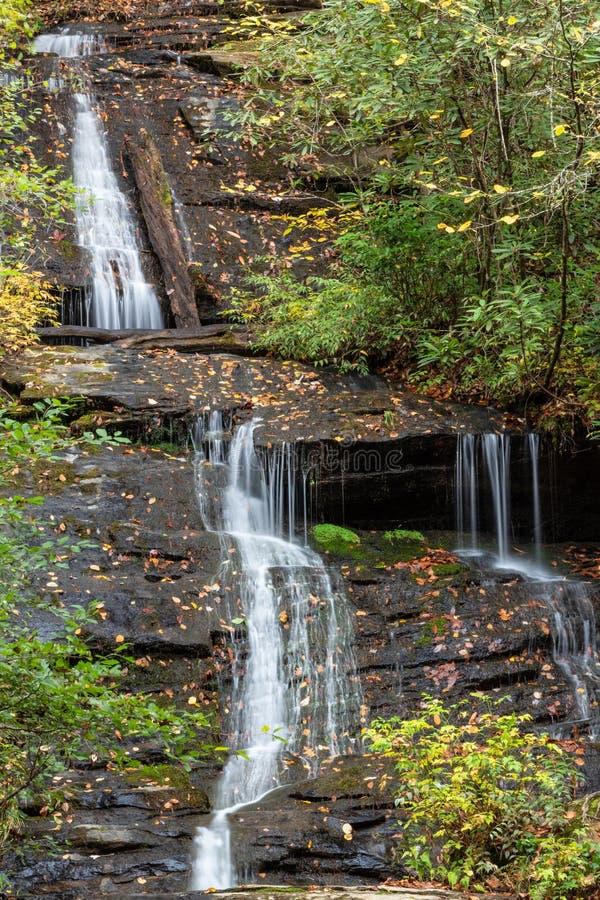 Multi tiered водопад через влажные утесы предусматриванные в листьях и мхе осени стоковые фото