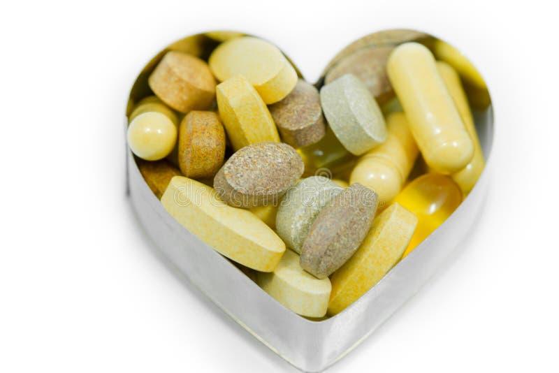 Multi Vitamin pills in heart isolated royalty free stock photos