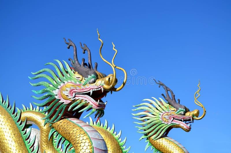 Multicolor de dos estatuas chinas del dragón contra el cielo azul foto de archivo libre de regalías