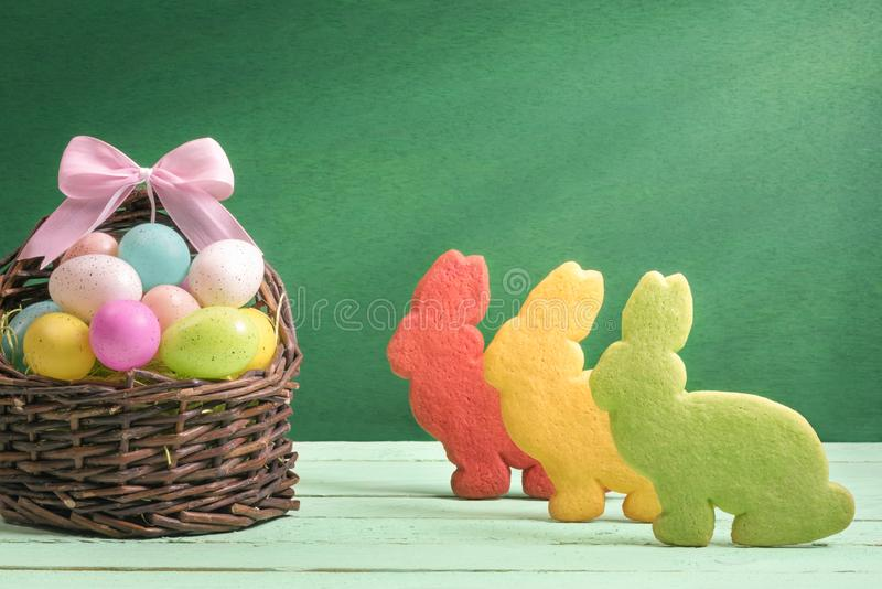 Multicolor Easter eggs and bunny shaped cookies royalty free stock photos