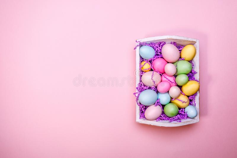 Multicolor eggs in a white tray. Creative Easter concept. Modern. Solid pink background. Horizontal stock photo