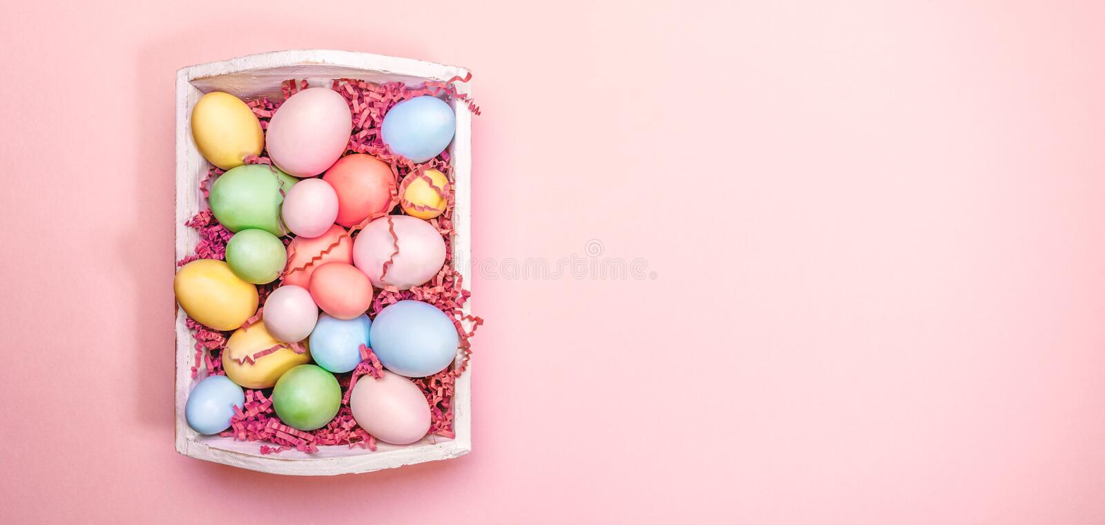 Multicolor eggs in a white tray. Creative Easter concept. Modern solid pink background. Living coral accent, color of the year. Multicolor eggs in a white tray royalty free stock images