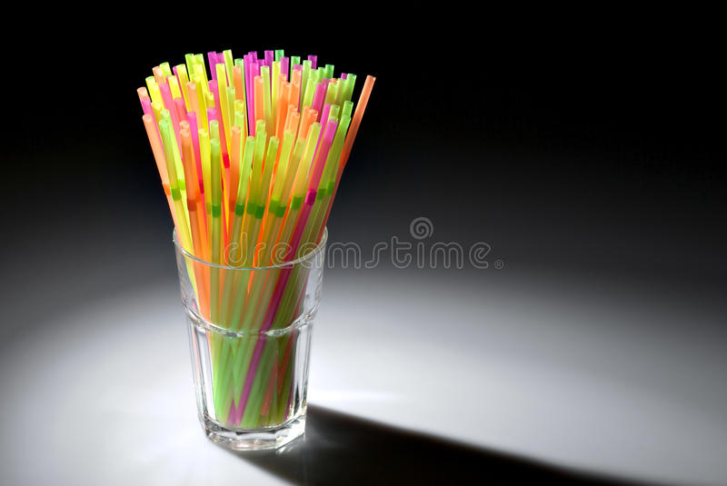 Multicolor flexible straws in the glass. In spot of light isolated on black background stock image