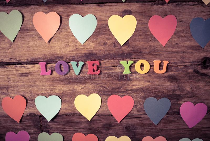 Multicolor hearts on wood background and text Love you for Valentine day and love celebration stock photography