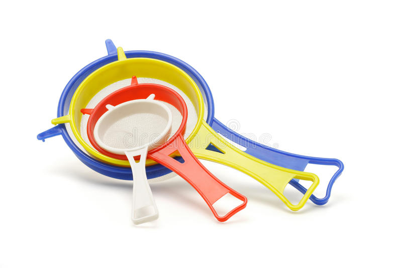 Multicolor kitchen sieves. Of various sizes on white background royalty free stock photo